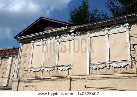 Facade of old vintage house with boarded up windows in white frame in rural city horizontal photo closeup