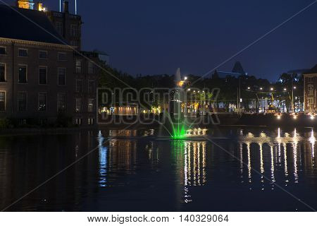 View on the Hofvijver with fountain at the Dutch Parliament Building 'het Binnenhof' in the Hague the Netherlands at night