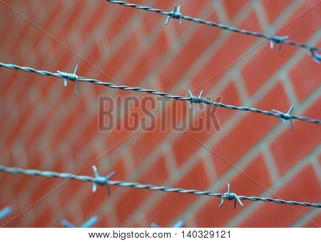 barbed fence jail and red brick wall