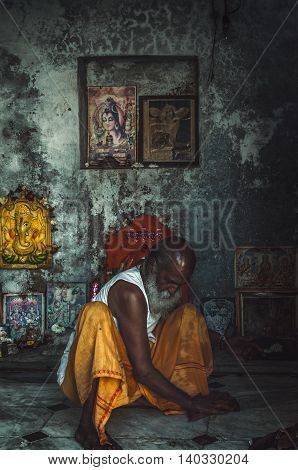 Pushkar Rajasthan India - February 16 2015 : A shot of a person cleaning the floor of a mini worship place.The shot was taken at Pushkar India.