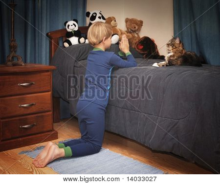 boy kneeling at bedside saying prayers in pajamas