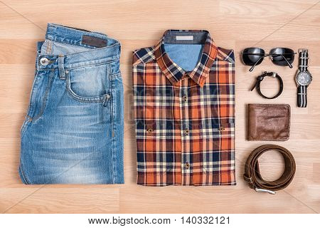 Men casual outfits with accessories on wooden table Blue and orange plaid shirt and jeans with eyeglasses bracelet wallet brown belt and watch top view
