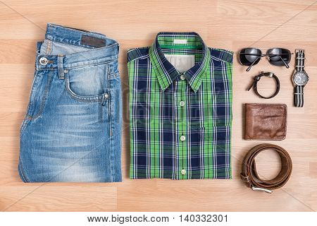 Classic men casual outfits fashionable with accessories on wooden table Blue and green plaid shirt and jeans with eyeglasses bracelet wallet brown belt and watch top view