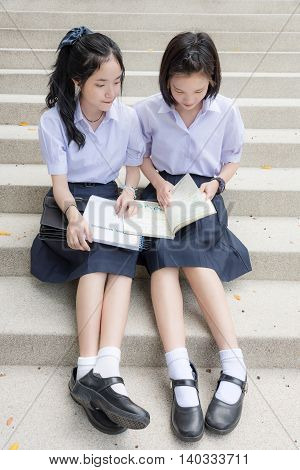 Cute Asian Thai high schoolgirls student couple in school uniform sit on the stairway discussing homework or exam with a happy smiling face together on a building stairs