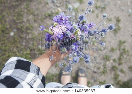 bouquet of blue wildflowers in female hand
