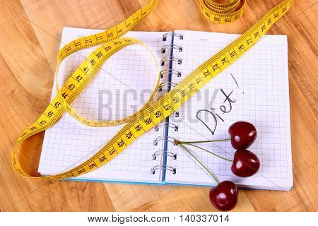 Fresh cherry and tape measure with notebook for writing notes concept of slimming diet and healthy nutrition
