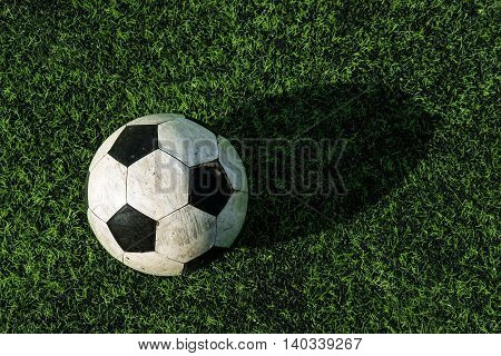 Old soccer ball on green grass, with shade and shadow