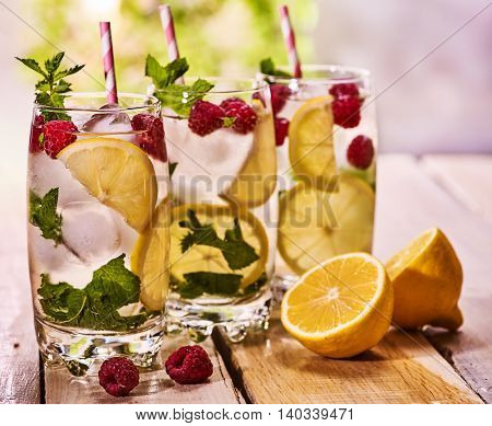 Wooden boards group of glasses with alcohol cocktail and ice cubes. Drink two hundred ninety three cocktail raspberry mohito with straw and lemon and mint leaf. Still life. Outdoor. Light background.