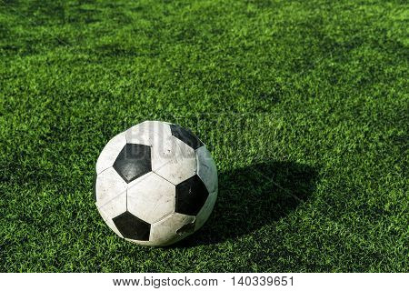 Old soccer ball on green grass with shadow