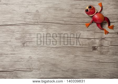 Jumping frog made of apple on wooden background