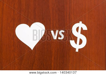 Love vs money paper signs. Abstract conceptual image. Wooden background