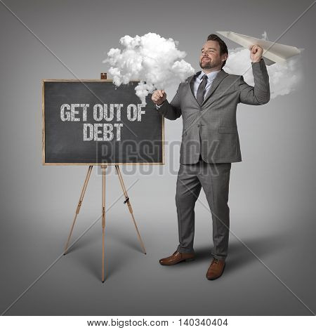 Get out of debt text on blackboard with businessman and paper plane