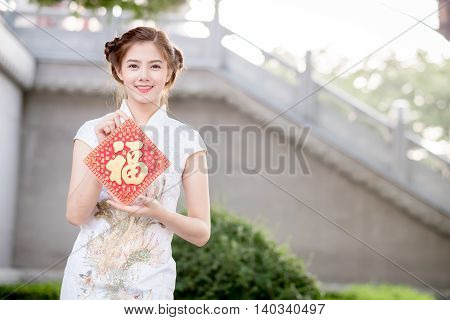 The Asian Woman In Chinese Dress Holding Couplet 'happy.' (chinese Blessing Word) With Chinese Templ