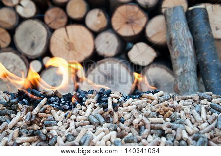 Burning pellets in front pile of wood