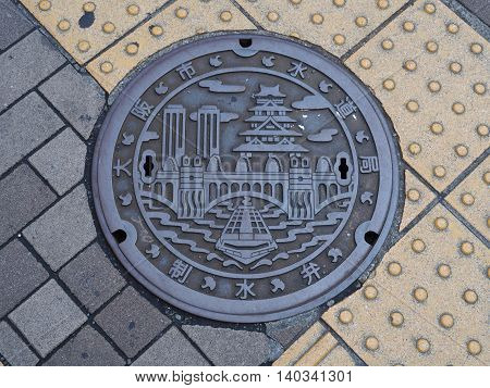 OSAKA, JAPAN - JUNE 08, 2016: A manhole cover in Osaka, Japan. A ship on Dotonbori canal and Osaka castle engraved on to a manhole cover as a symbol of an important city's landmark.