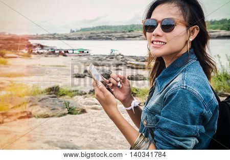 Asian women have used maps from a mobile phone with joyful mood.