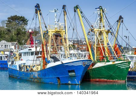 Rusty fishing trawlers moored in the port of a small fishing village