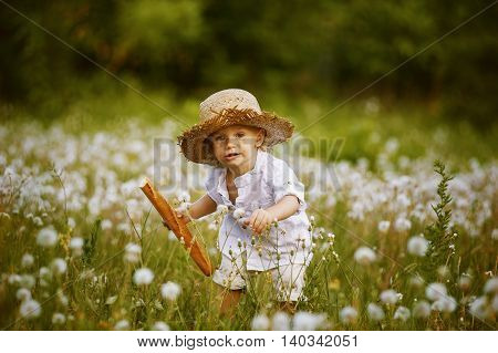 Little boy in field with dandelions , and French bread in his hands