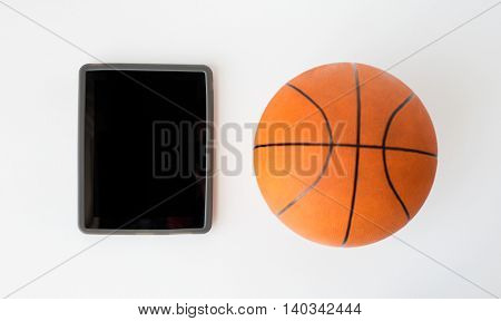 sport, fitness, game, sports equipment and technology concept - close up of basketball ball and tablet pc computer with black blank screen on white background