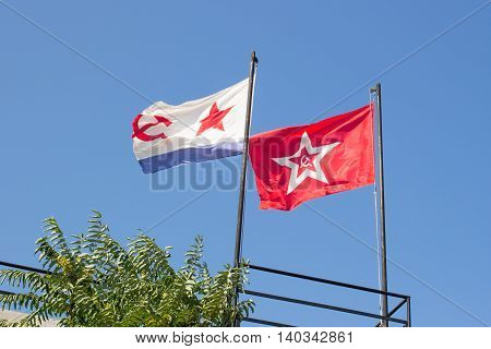 two flags fluttering in the wind against the sky