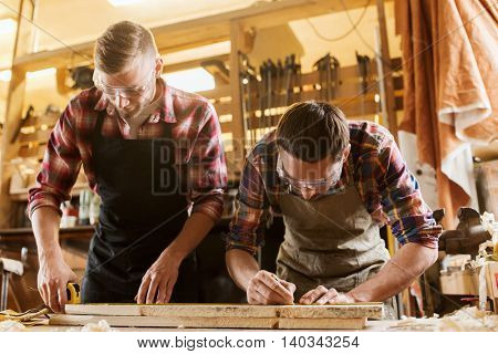 profession, carpentry, woodwork and people concept - two carpenters with ruler measuring wood plank at workshop