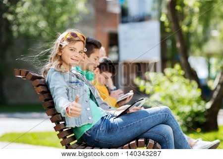 technology, internet and people concept - happy girl with tablet pc computer showing thumbs up and group of teenage friends or students outdoors