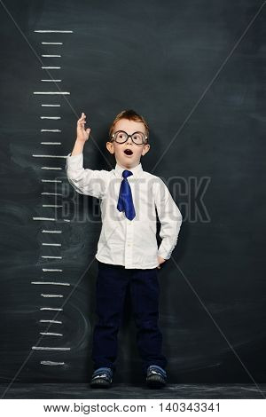 Four year old boy in white shirt and a tie standing by a stadiometer, drawn on a blackboard. Education.
