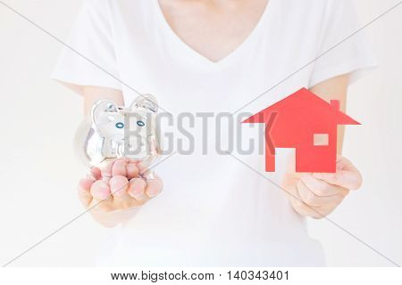 Hands holding a piggy bank and a house model.