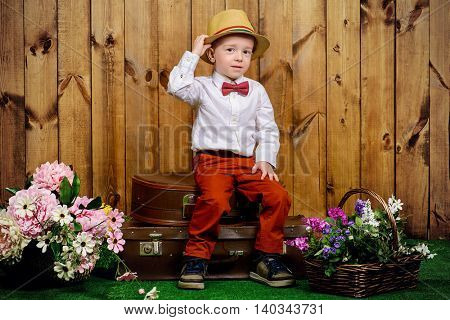Cute little boy in elegant clothes sitting on his old suitcases on a green lawn with flowers over wooden background. Kid's fashion. Childhood. Summer holidays.