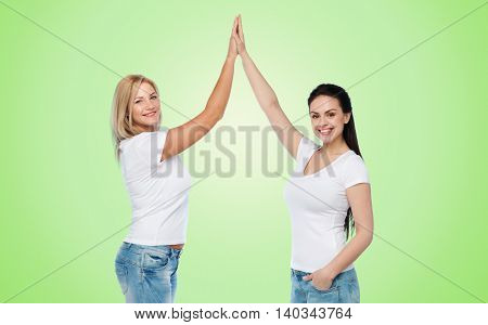 friendship, diverse, body positive, gesture and people concept - group of happy different women in white t-shirts making high five over green natural background