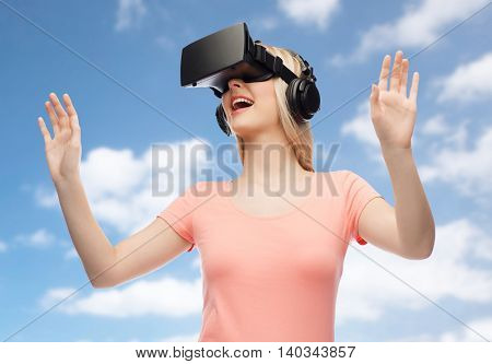 technology, virtual reality, entertainment and people concept - happy young woman with virtual reality headset or 3d glasses and headphones playing game over blue sky and clouds background