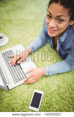 High angle portrait of businesswoman using laptop while lying on carpet in creative office