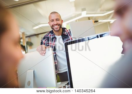 Portrait of smiling businessman with colleagues in creative office