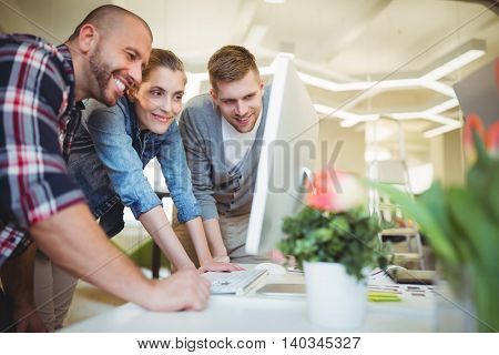 Smiling business people looking at computer in creative office