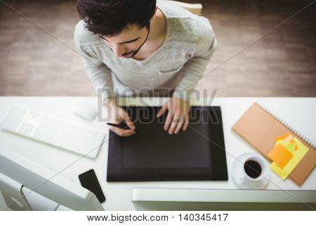 High angle view of businessman using graphics tablet in creative office