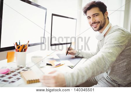 Portrait of businessman working at desk in creative office