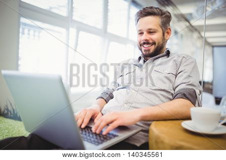 Smiling businessman working on laptop in creative office