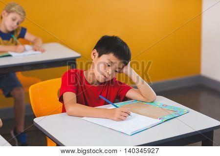 Schoolboy doing her homework in classroom at school