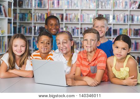 Portrait of school kids using laptop in library at school