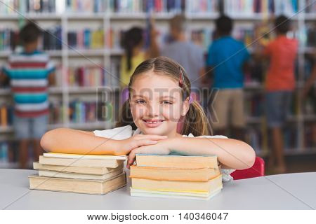 Smiling girl leaning on pile of books in library at elementary school