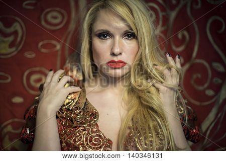 blonde dressed in red armor gold on red art nouveau flourishes