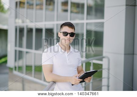 Portrait of a young businessman with tablet pc on the street. Man with dark sunglasses.
