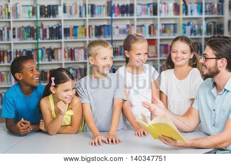 Teacher and kids reading book in library at elementary school