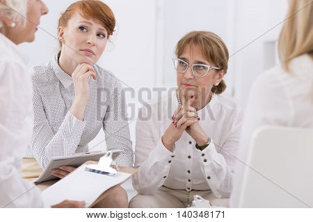 Shot of female employees listening carefully during a meeting