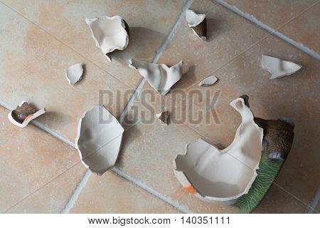 decorative ceramics figure is broken on tile floor