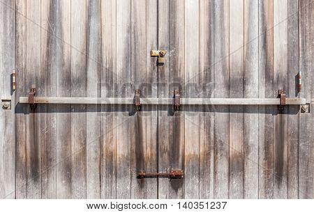 Wooden entrance door with rustic padlock retro style in farmland.