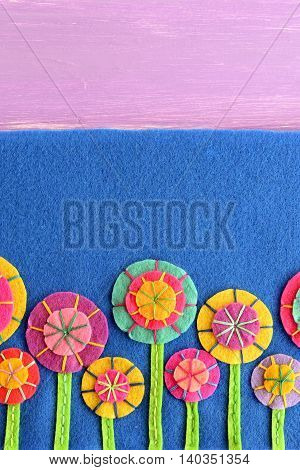 Mixed felt flowers on blue background with empty place for text. Variegated flower applique for kids. Floral greeting card for birthday, Easter, Valentine's day, mother's day