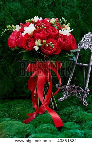 dense red bouquet of roses, tied with a red ribbon. Close