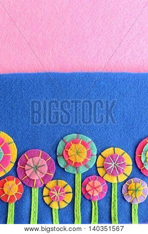 Colorful felt flowers set on a blue and pink background with copy space for text. Hand crafts cute flowers. Floral craft embellishments. Festive greeting card for mother's day, birthday