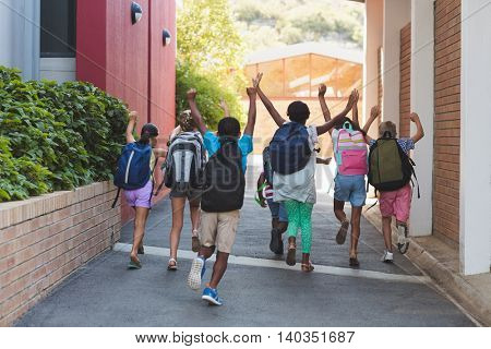 Rear view of playful classmates running at school campus